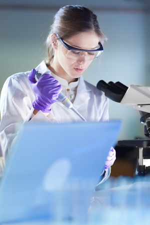 health care professional: Life scientist researching in laboratory. Portrait of attractive, young, confident female health care professional pipetting under microscope in hes working environment. Healthcare and biotechnology.