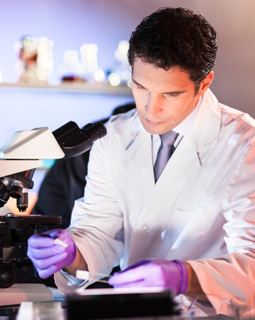 dental research: Life scientist researching in laboratory. Attractive young male scientist looking at the microscope slides in laboratory. Healthcare and biotechnology concept.