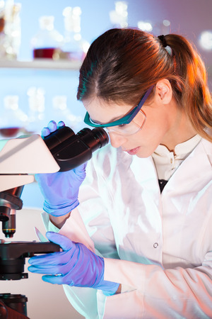 healthcare portrait: Life scientist researching in laboratory. Portrait of a attractive, young, confident female health care professional microscoping in hes working environment. Healthcare and biotechnology.