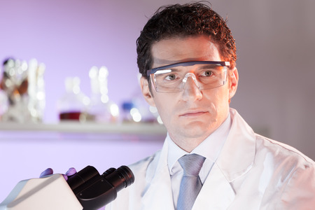 health care professional: Portrait of a attractive, young, confident male health care professional with microscope in hes working environment. Healthcare and biotechnology.