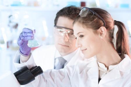 investigador cientifico: Científico vida investigando en el laboratorio. Científico joven atractivo y su supervisor de post doctorado mirando el portaobjetos de un microscopio en el laboratorio forense. Salud y biotecnología. Foto de archivo