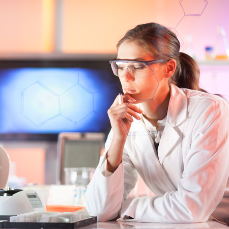 health woman: Life science researcher working in laboratory. Portrait of a confident female health care professional in his working environment reviewing structural chemical formula written on a glass board.