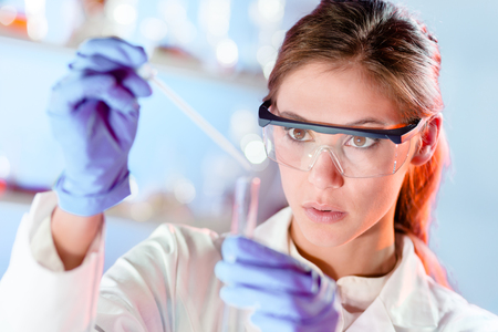 Life scientists researching in laboratory. Focused female life science professional pipetting solution into the glass cuvette. Lens focus on researcher's eyes. Healthcare and biotechnology concept.