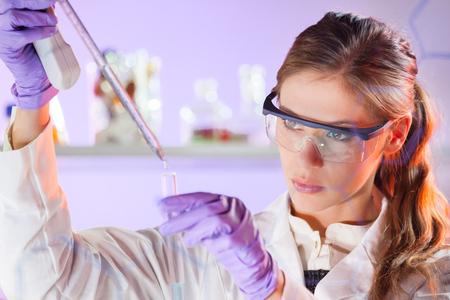 investigador cientifico: Cient�ficos vida investigando en el laboratorio. Ciencias de la vida femenina soluci�n pipeta profesional enfocada en la cubeta de vidrio. Enfoque de la lente en los ojos del investigador. Salud y concepto de la biotecnolog�a. Foto de archivo