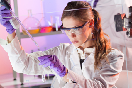 Científicos vida investigando en el laboratorio. Ciencias de la vida femenina solución pipeta profesional enfocada en la cubeta de vidrio. Enfoque de la lente en los ojos del investigador. Salud y concepto de la biotecnología.