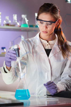 researchers: Life scientists researching in laboratory. Focused female life science professional pipetting blue solution into glass cuvette. Lens focus on researchers eyes. Healthcare and biotechnology concept.