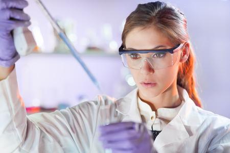 bata de laboratorio: Científicos vida investigando en el laboratorio. Ciencias de la vida femenina solución pipeta profesional enfocada en la cubeta de vidrio. Enfoque de la lente en los ojos del investigador. Salud y concepto de la biotecnología. Foto de archivo