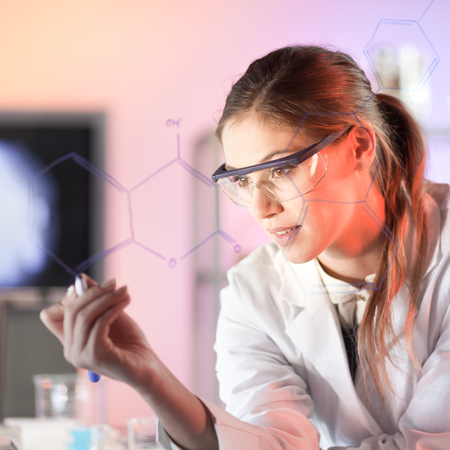 wise woman: Life science researcher working in laboratory. Portrait of a confident female health care professional in his working environment writing structural chemical formula on a glass board.