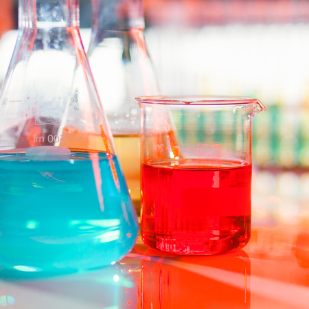 square composition: Backlit laboratory test flask containing colorful liquids. Square composition.