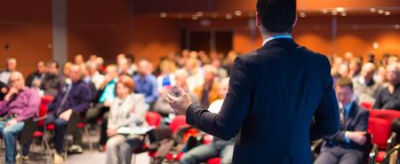 orador: Ponente en la Conferencia de negocios con presentaciones públicas. Audiencia en la sala de conferencias. Club de Emprendimiento. Vista trasera. Composición panorámica. Desenfoque de fondo.