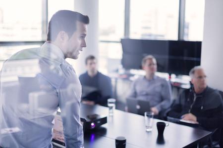 Business man làm một bài thuyết trình tại văn phòng. Điều hành kinh doanh cung cấp một bài thuyết trình cho các đồng nghiệp của ông trong cuộc họp hoặc trong nhà đào tạo kinh doanh, giải thích kế hoạch kinh doanh cho nhân viên của mình.