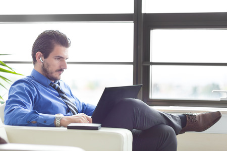 teleconference: Busy, focused businessman in office working on his laptop wearing headphones. Side view. Stock Photo