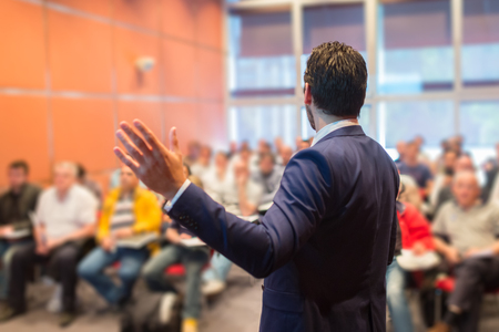 Speaker at Business Conference with Public Presentations. Audience at the conference hall. Entrepreneurship club. Rear view. Horisontal composition. Background blur.