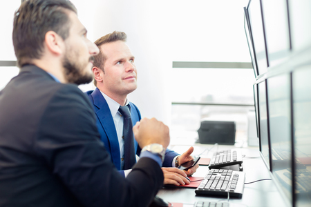 stock traders: Successful businessmen trading stocks. Stock traders looking at graphs, indexes and numbers on multiple computer screens. Colleagues in traders office. Business success. Stock Photo