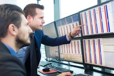 Geschäftsleuten den Handel mit Aktien. Aktienhändler suchen Sie in Graphen, Indizes und Zahlen auf mehreren Bildschirmen. Kolleginnen und Kollegen in der Diskussion in Händler Büro. Wirtschaftlicher Erfolg Konzept.