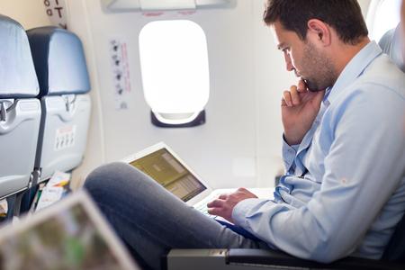 travel: Niedbale ubrany mężczyzna w średnim wieku pracy na laptopie w kabinie samolotu podczas jego podróży służbowej. Płytkie głębi pola Zdjęcie z naciskiem na biznesmena oka.