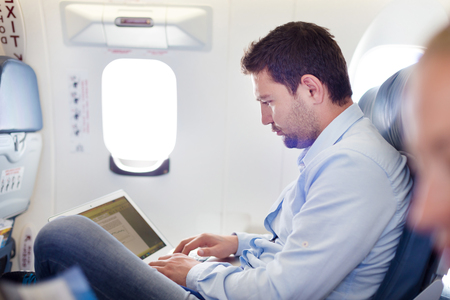 transport interior: Casually dressed middle aged man working on laptop in aircraft cabin during his business travel. Shallow depth of field photo with focus on businessman eye.