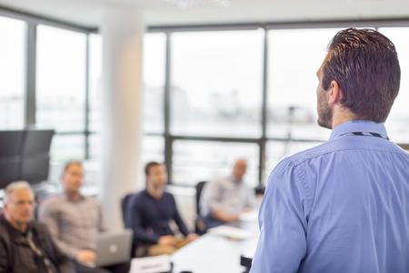 utbildning: Affärsman göra en presentation på kontoret. Företagsledare leverera en presentation till sina kolleger under möte eller intern företagsutbildning, förklarar affärsplaner för sina anställda. Stockfoto