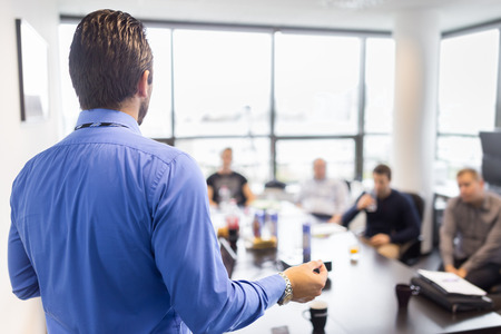 manager: Business man making a presentation at office. Business executive delivering a presentation to his colleagues during meeting or in-house business training, explaining business plans to his employees. Stock Photo