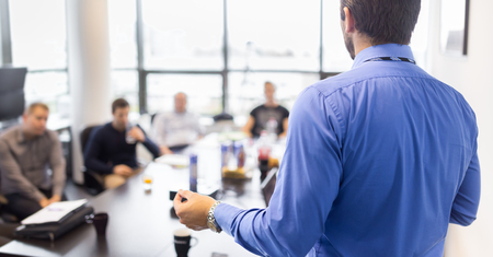 training group: Business man making a presentation at office. Business executive delivering a presentation to his colleagues during meeting or in-house business training, explaining business plans to his employees. Stock Photo