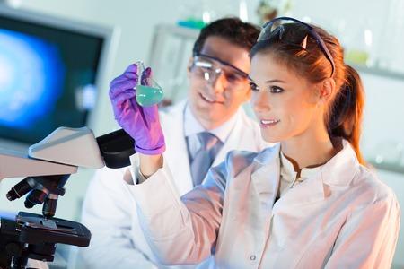 bata de laboratorio: Qu�mica escena de laboratorio: atractiva joven estudiante y su puesto cient�fico director de tesis observando la soluci�n indikator cambio de color verde en frasco de vidrio. Foto de archivo