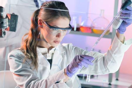 Científicos vida investigando en el laboratorio. Ciencias de la vida femenina solución pipeta profesional enfocada en la cubeta de vidrio. Enfoque de la lente en los ojos del investigador. Salud y concepto de la biotecnología. Foto de archivo