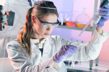 laboratory coat: Life scientists researching in laboratory. Focused female life science professional pipetting solution into the glass cuvette. Lens focus on researchers eyes. Healthcare and biotechnology concept. Stock Photo