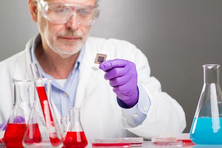 carga: Enfocado ciencias de la vida profesional de alto nivel de retención y observando el micro chip. Enfoque del objetivo en el chip. Foto de archivo