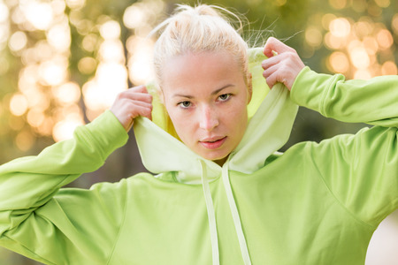 urban jungle: Portrait of attractive confident sporty woman wearing fashionable green hoodie while training in the nature. Active lifestyle and sportswear concept. Stock Photo