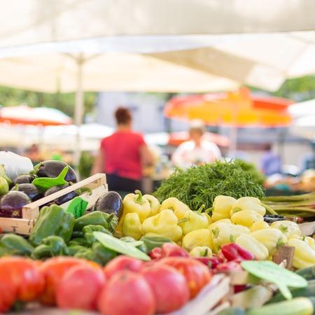 agricultor: Puesto en el mercado de alimentos de los agricultores con la variedad de vegetales orgánicos. Vendedor servir y charlando con los clientes.