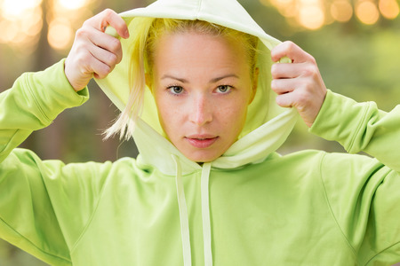 hair tuft: Portrait of attractive confident sporty woman wearing fashionable green hoodie while training in the nature. Active lifestyle and sportswear concept. Stock Photo