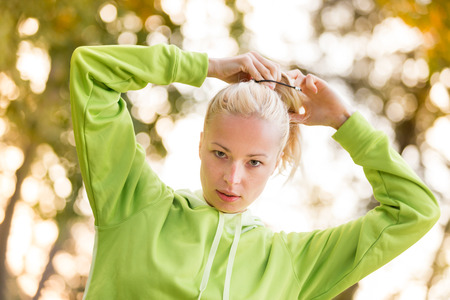 hair tuft: Portrait of attractive confident sporty woman wearing fashionable green sportswear  making her hair in ponytail before training in nature. Active sporty lifestyle concept.
