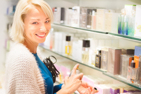 retail store: Casual blond young woman smelling perfume in retail store. Beautiful blond lady testing  and buying cosmetics in a beauty store.