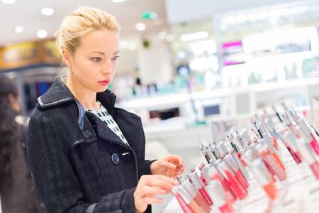 mujer maquillandose: Prueba rubia hermosa dama y cosm�ticos que compran en una tienda de belleza.