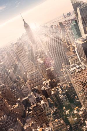 New York City. Manhattan skyline van het centrum met verlichte Empire State Building en wolkenkrabbers bij zonsondergang. Verticale samenstelling. Warme avond kleuren. Zonnestralen en lens flare.