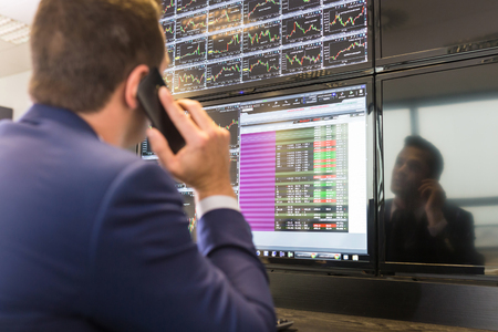 Businessman with cell phone trading stocks. Stock analyst looking at graphs, indexes and numbers on multiple computer screens. Stock trader evaluating economic data. Stock Photo