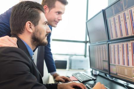 stock traders: Gli uomini d'affari trading stock. Operatori di borsa guardando i grafici, indici e numeri su pi� schermi di computer. Colleghi in discussione in ufficio commercianti. Concetto di successo di affari.