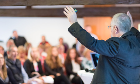 predicador: Ponente en la Conferencia de negocios con presentaciones públicas. Audiencia en la sala de conferencias. Vista trasera. Composición Horisontal. Desenfoque de fondo.