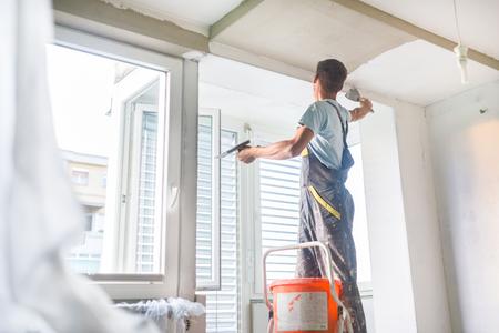 pintor: Treinta años trabajador manual con herramientas muro enlucido interior de una casa. Yesero renovación de paredes y techos interiores con flotador y yeso.