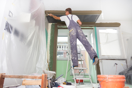 wall covering: Thirty years old manual worker with wall plastering tools inside a house. Plasterer renovating indoor walls and ceilings with float and plaster. Stock Photo