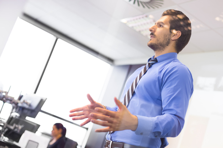 Business man making a presentation at office. Business executive delivering a presentation to his colleagues during meeting or in-house business training. Business and entrepreneurship. Stock Photo