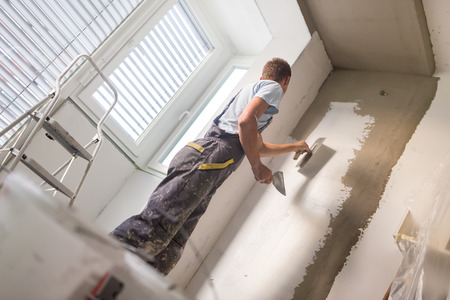 Thirty years old manual worker with wall plastering tools inside a house. Plasterer renovating indoor walls and ceilings with float and plaster. Stockfoto
