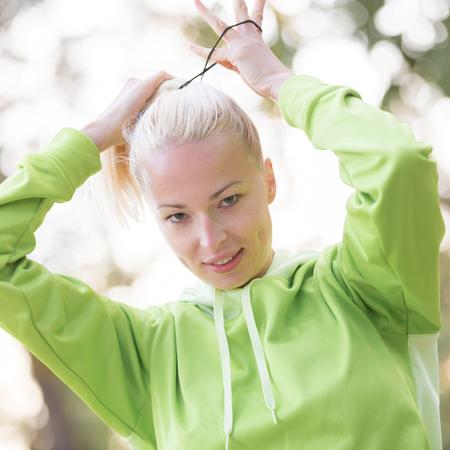 cabello rubio: Retrato de la atractiva mujer deportiva confiado usándolo moda ropa deportiva verde haciendo el pelo recogido en cola de caballo antes del entrenamiento en la naturaleza. Concepto de estilo de vida deportiva activa.