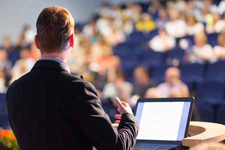 Spreker bij bedrijfsconferentie met publieke presentaties. Publiek in de vergaderzaal. Ondernemersclub. Achteraanzicht. Horizontale samenstelling. Achtergrond vervaging.