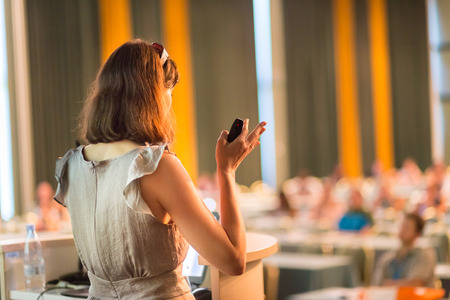 orador: Altavoz Mujer en la Conferencia de negocios y presentación. Audiencia en la sala de conferencias. Negocios y Emprendimiento. Mujer de negocios. Composición horizontal.