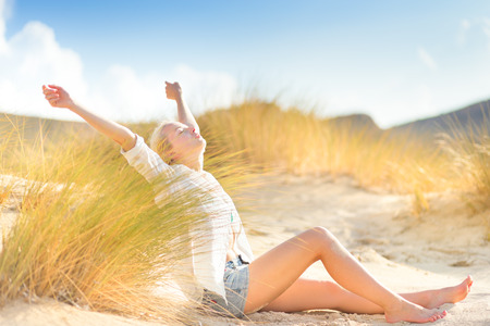 feeling happy: Relaxed woman enjoying freedom and life in beautiful natural environment. Blissful girl raising arms, feeling free, relaxed and happy. Concept of freedom, happiness, enjoyment and natural balance. Stock Photo