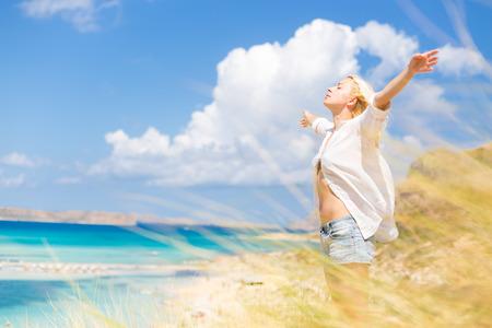 자유와 생활하는 A 아름다운 모래 해변을 즐기는 편안한 여자. 젊은 아가씨, 팔을 제기, 무료 편안하고 행복한 느낌. 자유, 행복, 즐거움과 웰빙의 개념 스톡 콘텐츠