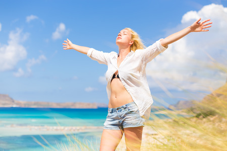 relaxing beach: Relaxed woman enjoying freedom and life an a beautiful sandy beach.  Young lady raising arms, feeling free, relaxed and happy. Concept of freedom, happiness, enjoyment and well being. Stock Photo