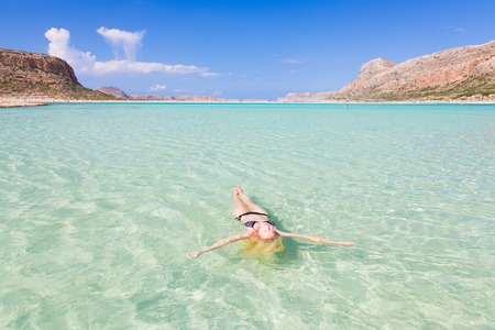 lagoon: Beautiful Caucasian woman floating in turquoise blue lagoon.
