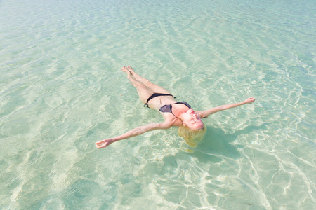 float: Beautiful Caucasian woman floating in turquoise blue lagoon.